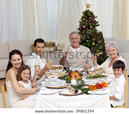 Family tusting with white wine in a Christmas dinner at home - stock photo