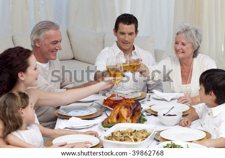 Family tusting with wine in a dinner at home - stock photo