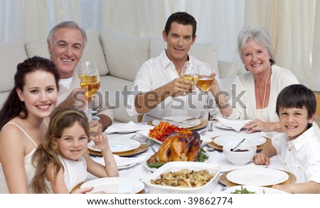 Family tusting with wine in a dinner at home smiling at the camera - stock photo