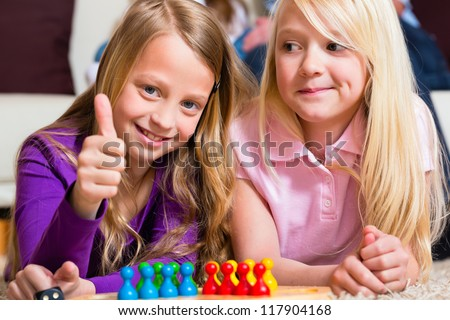 Family - two sisters - playing board game ludo at home on the floor, focus on dice in the front - stock photo