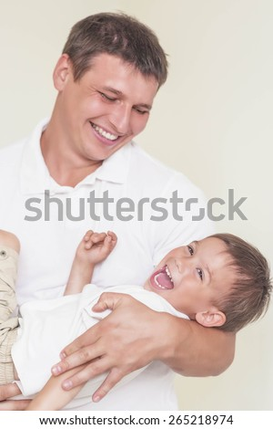 Family Union Concept: Dad and Son Together Playing and Having Great Time. Indoors Shot. Vertical Image - stock photo