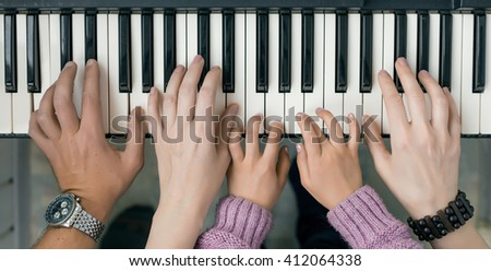 Family Unity Concept Image - Piano Keyboard top View and Hands of Child Mother and Father playing music