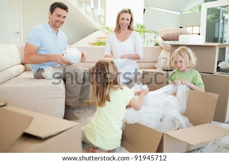 Family unpacking cardboard box in the living room together - stock photo