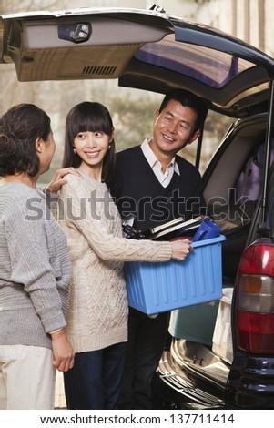 Family unpacking minivan for college, Beijing - stock photo