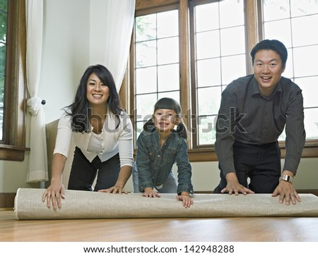 Family unrolling a rug in empty room - stock photo