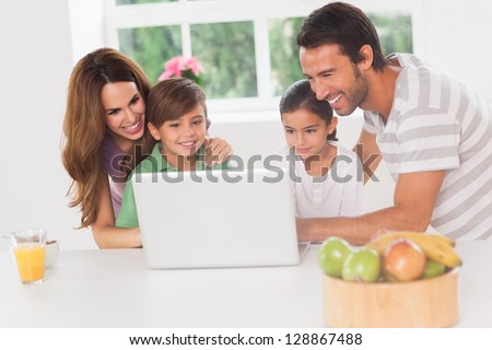 Family using a laptop in kitchen - stock photo