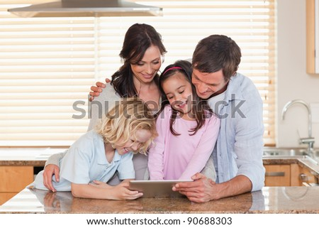 Family using a tablet computer together in a kitchen - stock photo