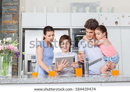 Family using a tablet pc in kitchen, parents with children happy smile, modern kitchen orange juice