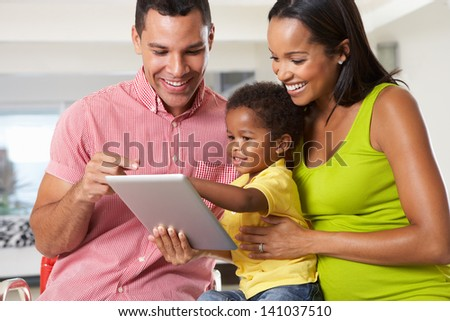 Family Using Digital Tablet In Kitchen Together - stock photo
