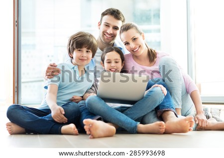 Family using laptop at home - stock photo