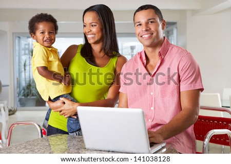Family Using Laptop In Kitchen Together - stock photo