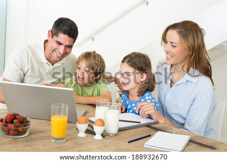 Family using laptop while having breakfast at home - stock photo