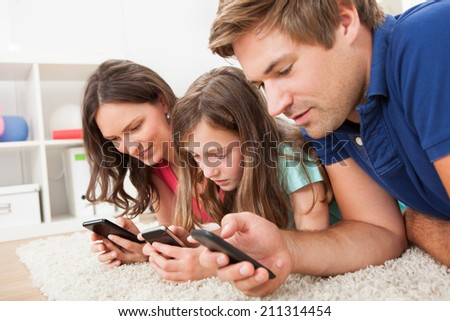 Family using smart phones while lying on rug at home - stock photo