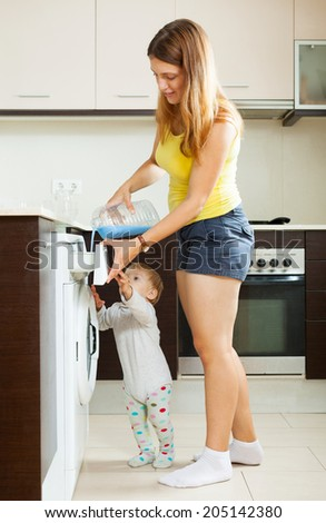 Family using washing machine with laundry detergent at home - stock photo