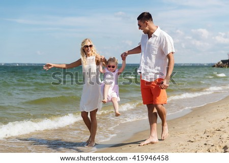 family, vacation, adoption and people concept - happy man, woman and little girl in sunglasses walking and having fun on summer beach - stock photo