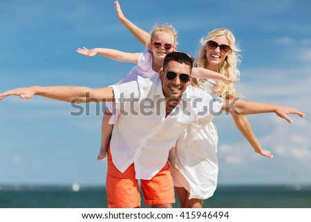 family, vacation, adoption and people concept - happy man, woman and little girl in sunglasses having fun on summer beach - stock photo
