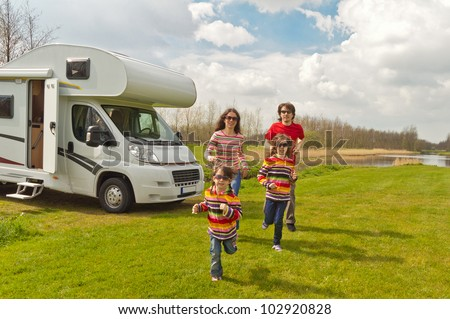 Family vacation in camping. Happy active parents with kids travel on camper (RV). Family having fun near their motorhome. Spring vacation trip with children. - stock photo