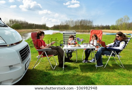 Family vacation in camping. Happy active parents with kids travel on camper (RV). Family having fun  and relaxing near their motorhome. Spring holiday trip with children. - stock photo