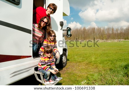 Family vacation in camping. Happy active parents with two kids travel on camper. Family having fun near their motorhome. Spring vacation trip with children. - stock photo