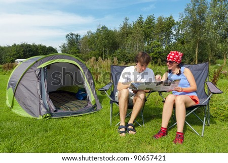 Family vacation in camping. Happy couple looking at map near their tent - stock photo