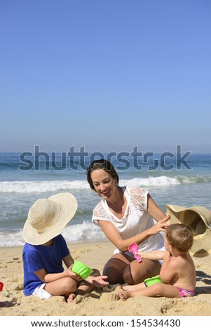 Family vacation on beach: Mother and kids playing in the sand - stock photo