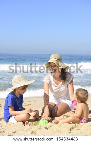 Family vacation on beach: Mother and kids playing in the sand