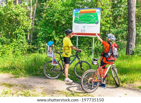 Family vacation on the bicycle. Caucasian happy family with bicycles is near map in the park.  Father and sons have biking helmet. The little boy is in the bicycle chair (seat) during ride.     - stock photo