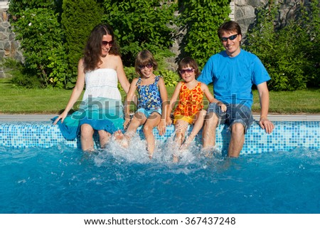 Family vacation, parents with two kids having fun near swimming pool