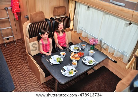 Family vacation, RV holiday trip, happy smiling kids travel on camper, children eating in motorhome interior
