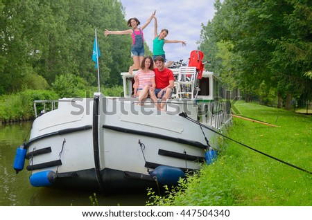 Family vacation, travel on barge boat in canal, happy parents with kids having fun on river cruise in houseboat  - stock photo