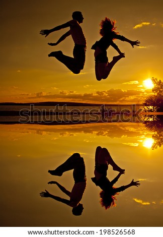 family vacations on the beach Silhouette of a couple - man and woman jumping on the beach on sunset cloudy sky with orange sun background with reflection on yellow water - stock photo