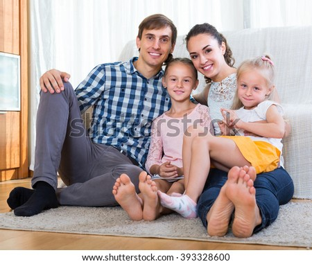Family values: portrait of happy parents 33s with little girls indoors