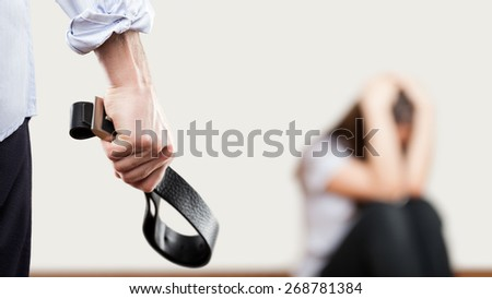 Family violence and aggression concept - furious angry man raised punishment hand holding leather belt over scared or terrified woman sitting at wall corner