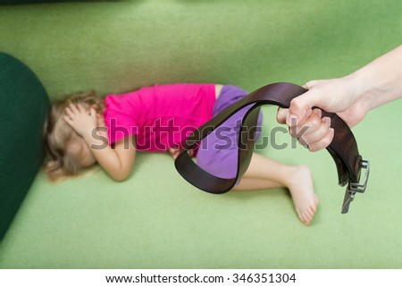 Family violence and aggression concept - furious angry man raised punishment hand holding leather belt over scared or terrified child - stock photo