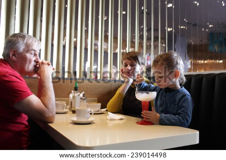 Family waits for son to finish eating ice cream in the cafe - stock photo