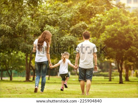 Family walk in the park, happy at sunset in Bangkok, Thailand. - stock photo
