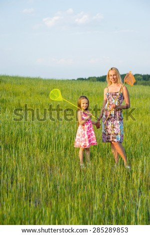 Family walk. Mom and daughter in the green grass.