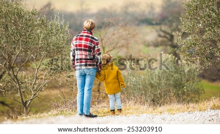 Family walk on the background of the marvelous Tuscan countryside. - stock photo