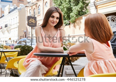 Family walk, two beautiful mother and young daughter sitting at an outdoor cafe at a table talking smiling stylish wear same dress green bush and chairs, summer caring for loved one, breakfast day off - stock photo
