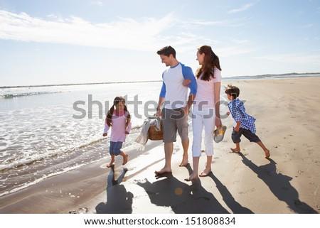 Family Walking Along Beach With Picnic Basket - stock photo