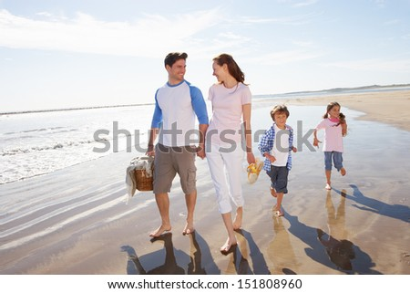 Family Walking Along Beach With Picnic Basket - stock photo