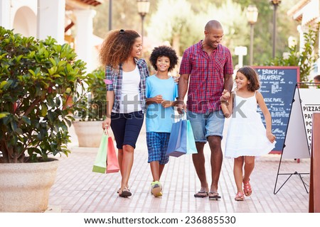 Family Walking Along Street With Shopping Bags - stock photo