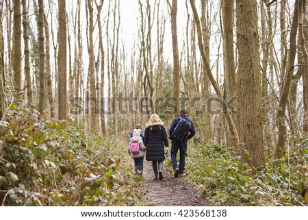 Family walking away from camera through a wood - stock photo