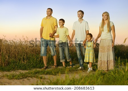 Family walking by road in field at sunset