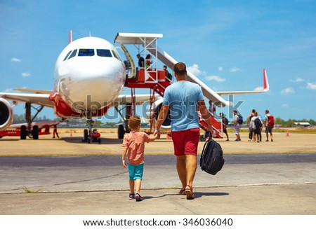 family walking for boarding on plane in airport, summer vacation - stock photo