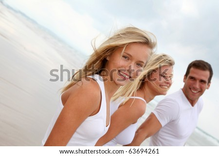 Family walking hand to hand on a sandy beach - stock photo