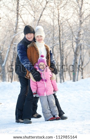 Family walking in a winter park. Parents with child
