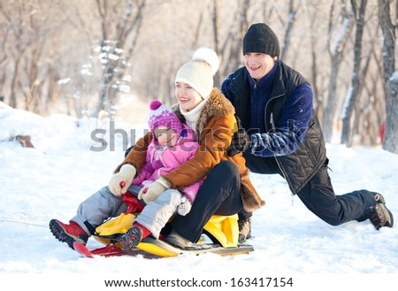 Family walking in a winter park. Parents with child on sled - stock photo