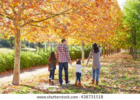 family walking in an autumn park with fallen fall leaves - stock photo