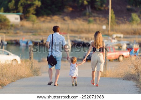 family walking on road at sunset - stock photo